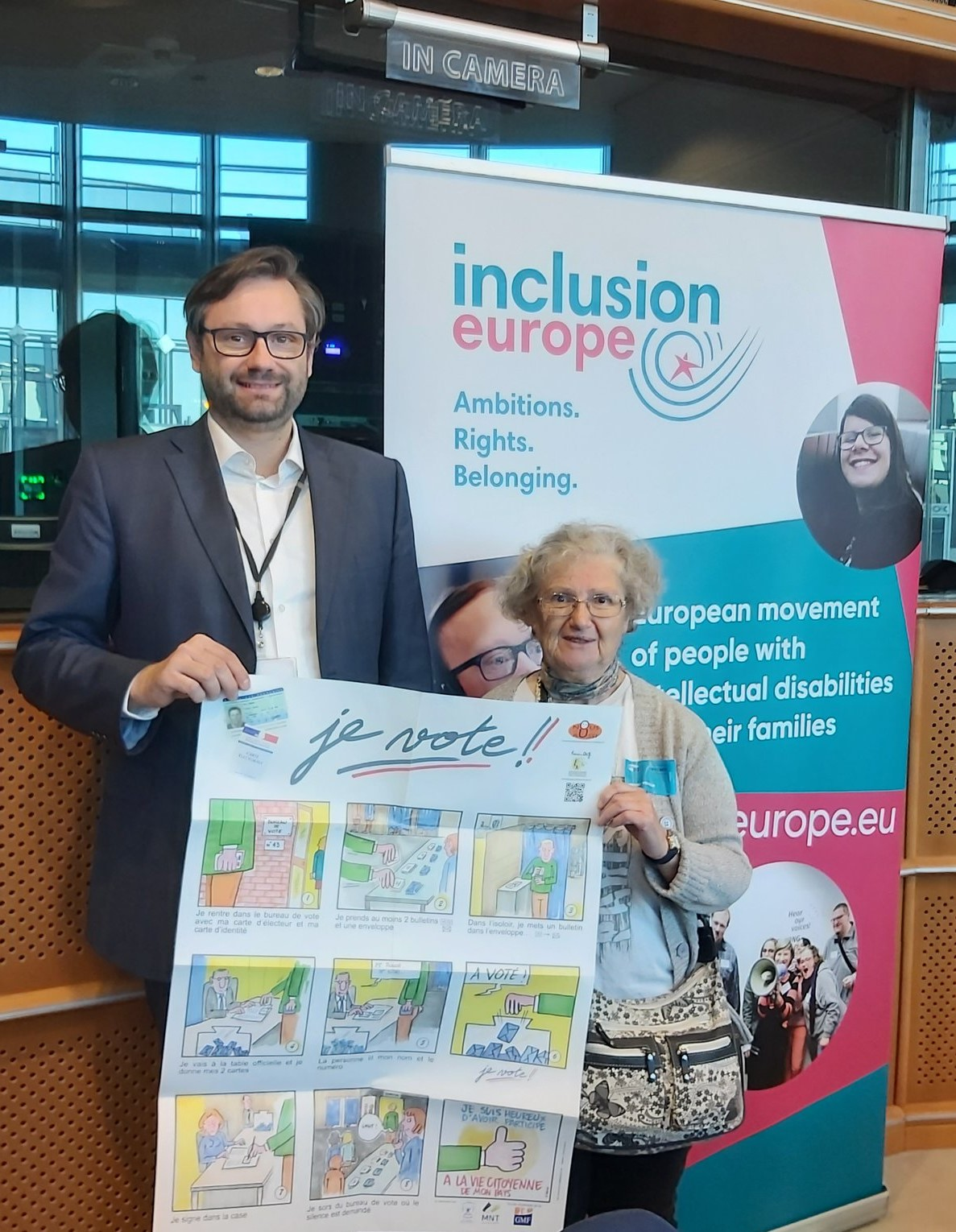 A tall man with glasses and an older woman with glasses standing in front of a banner, holding a poster